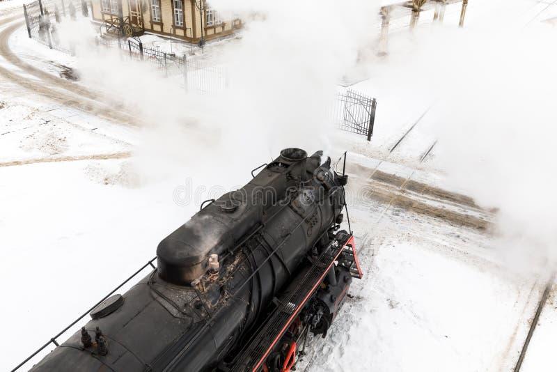 Alte schwarze Dampflokomotive in Russland im Winter auf einem Hintergrund des Schnees stockbild