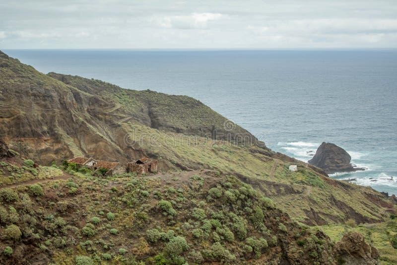 Alte scogliere ripide della roccia della lava sopra sull'est di Tenerife Rocce isolate che attaccano dall'acqua Vecchie capanne a fotografie stock libere da diritti