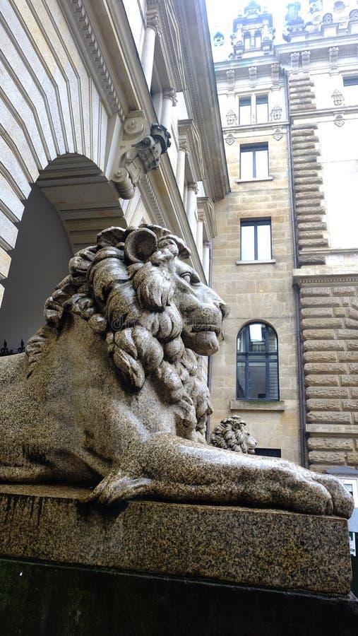 Alte Skulptur des Sitzens von Löwe Stein EL Nil Kairo-Kasr vor Musterhintergründen, starke Steinstatue stockbilder