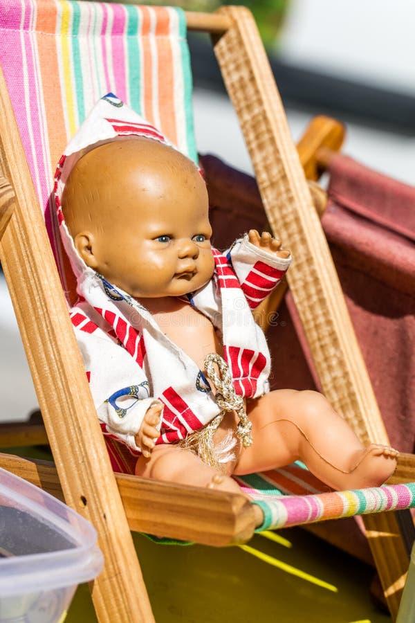Alte Sommerpuppe auf einem kleinen deckchair an der Straße angemessen lizenzfreie stockfotos