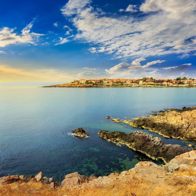 Alte Stadt auf einem felsigen Ufer nahe Meer bei Sonnenaufgang lizenzfreies stockbild