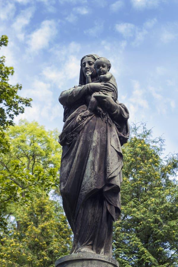 Alte Statue von Jungfrau Maria mit Baby auf Kirchhof lizenzfreie stockfotos