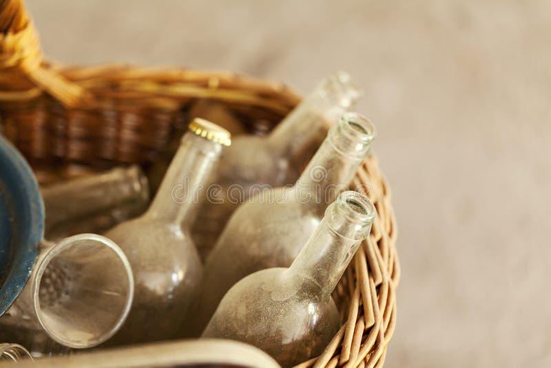 Alte staubige Glasflaschen in einem Weidenkorb stockfoto