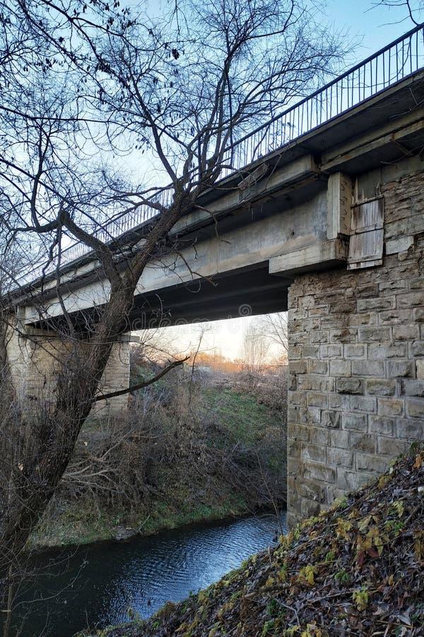 Alte Steinbrücke über einem flachen Fluss stockfotografie