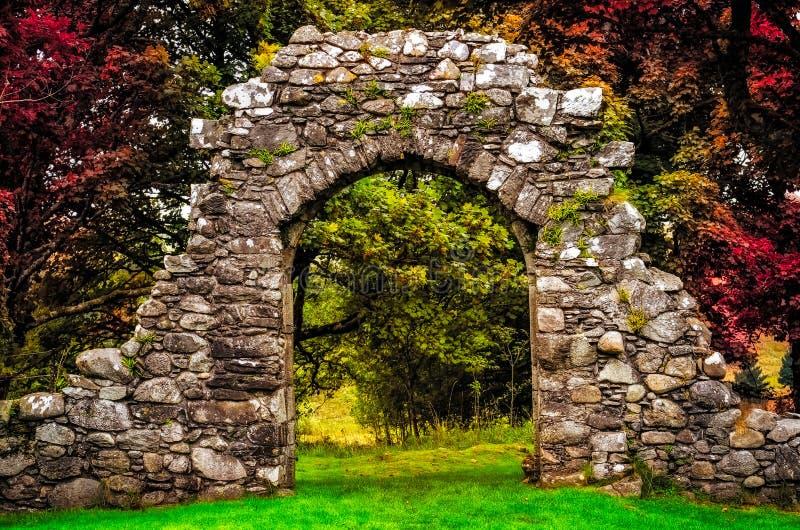 Alte Steineingangswand im Garten mit buntem Laub stockfoto