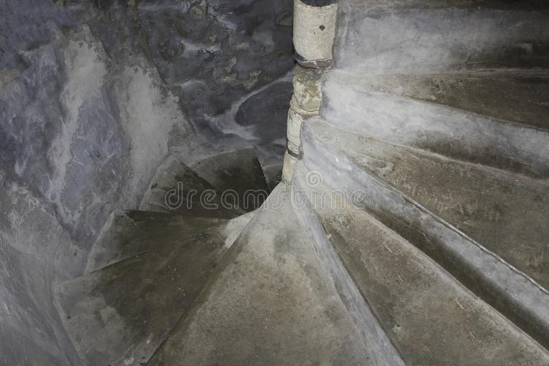 Alte, steinige Wendeltreppe, ein Schloss oder Festung, steigt unten in gruselige Dunkelheit ein lizenzfreie stockfotos