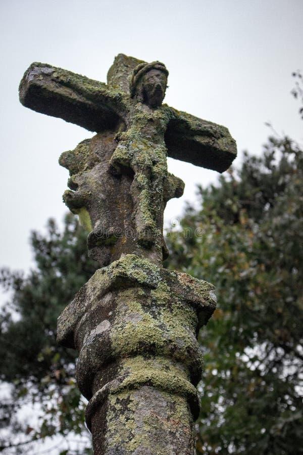 Alte Steinstatue mit ruinierter Zahl Jesuss Christus Mittelalterliche religiöse Skulptur Altes Kreuz mit Moos- und Jesus-Zahl stockfotos