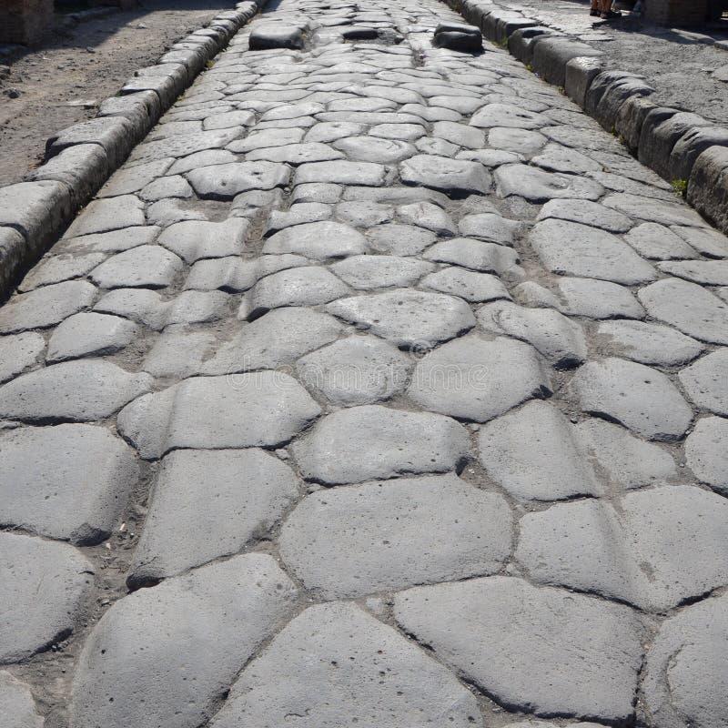 Alte Straße mit ursprünglichen Furchen im Stein, Pompeji lizenzfreie stockbilder