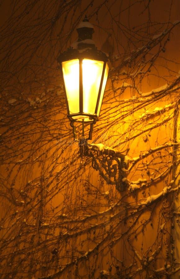 Alte Straßenlaterne auf einer Wand stockbilder