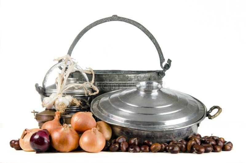 Alte Töpfe mit den Kastanien, Zwiebel und Knoblauch lokalisiert auf Weiß lizenzfreies stockbild