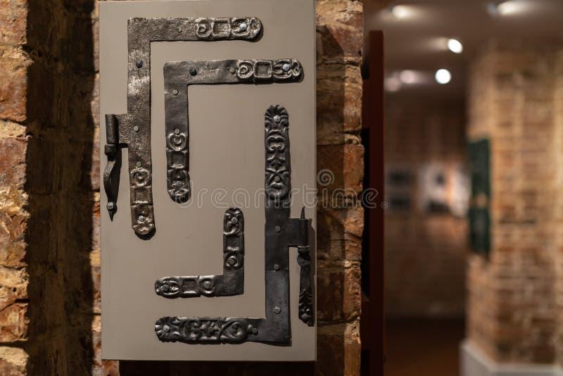 Alte Türlöcher und Griffe - hölzerner Eingang auf Backsteinmauern - Griffe hergestellt vom Metall stockfoto