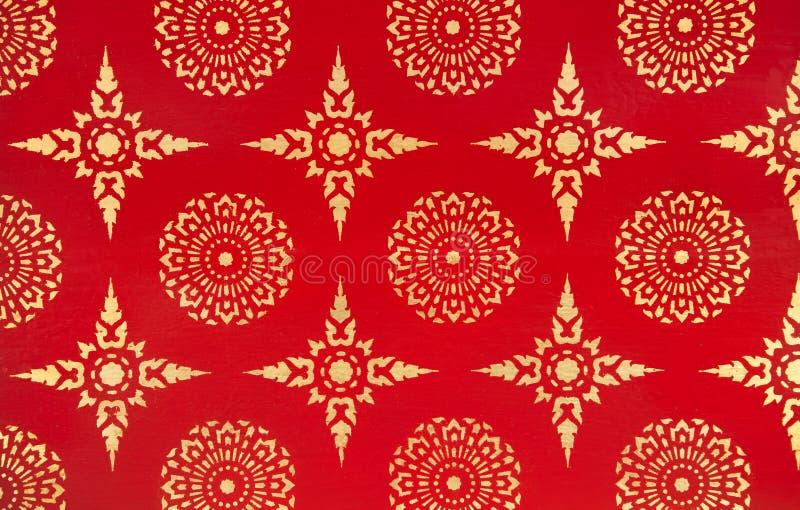 Alte traditionelle thailändische Design-Malerei mit goldenen Sternen und Blumen auf rotem Hintergrund stockfotografie
