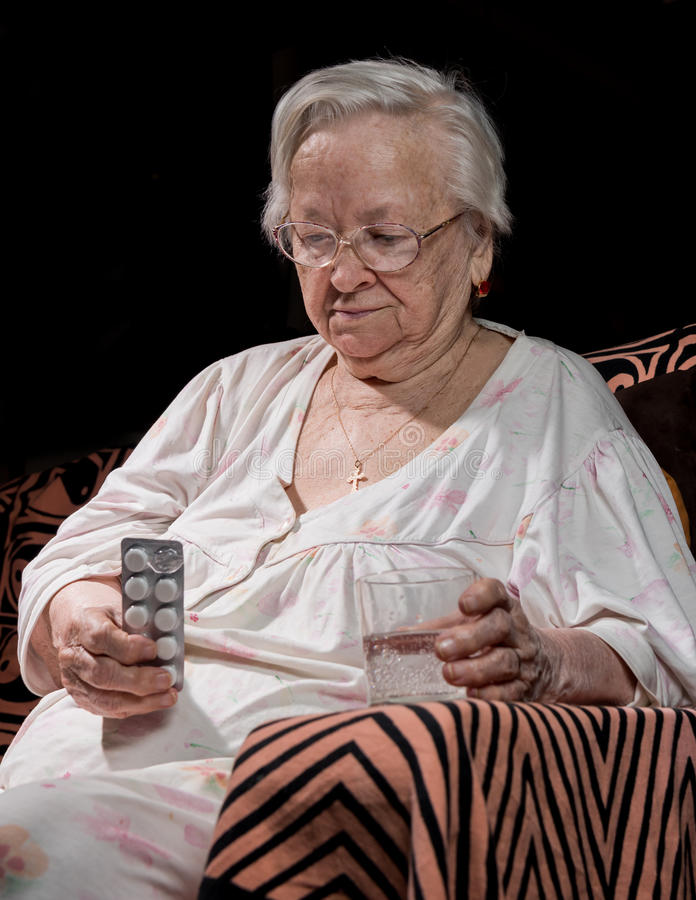 Alte traurige Frau, die Pillen hält stockbilder