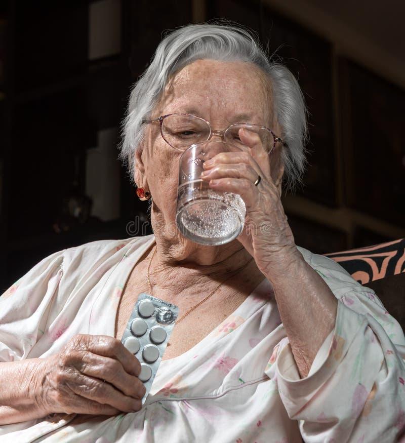 Alte traurige Frau, die Pillen hält stockfoto