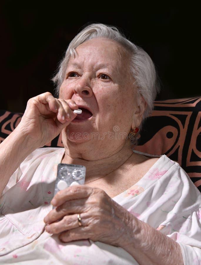 Alte traurige Frau, die Pillen hält lizenzfreies stockfoto