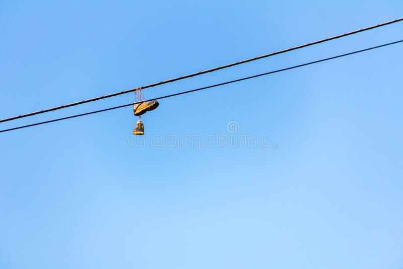 Alte Turnschuhe, die am elektrischen Draht mit blauem Himmel im Hintergrund hängen stockbilder