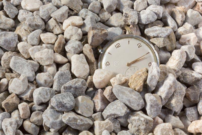 Alte Uhr, die vom Kies auftaucht stockfotografie