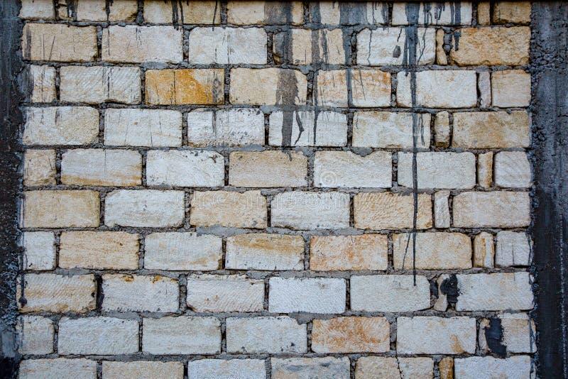 Alte und verwitterte grungy gelbe und weiße Backsteinmauer als nahtloser Musterbeschaffenheitshintergrund stockbild