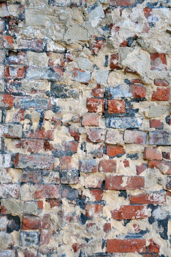 Alte verfallende Backsteinmauer mit Reparaturen und zerbröckelnder Zementschicht stockbilder
