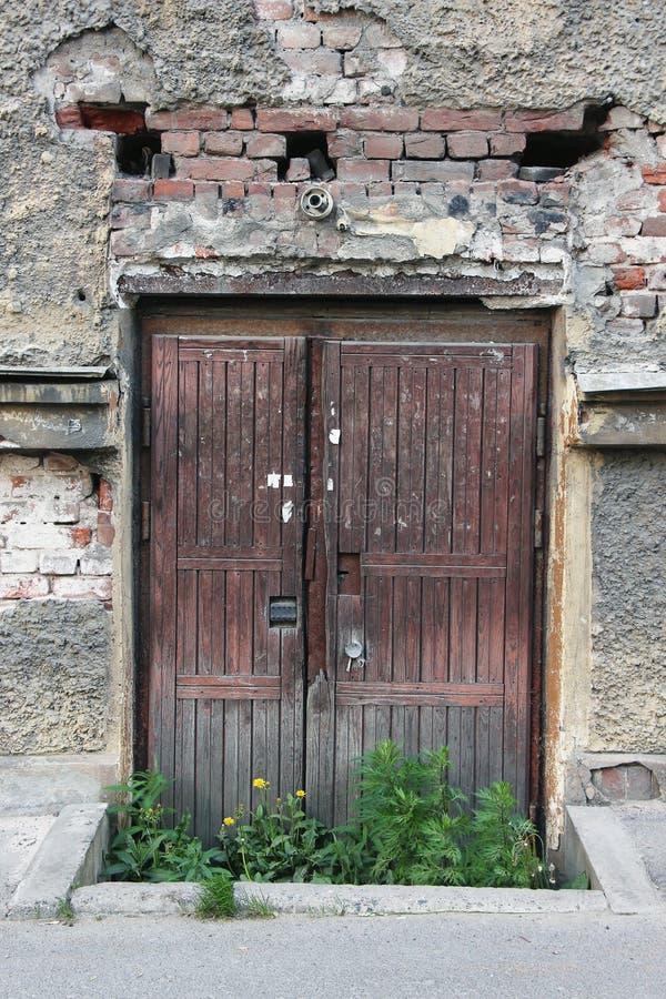 Alte verfallene Tür überwältigt mit Gras lizenzfreie stockbilder
