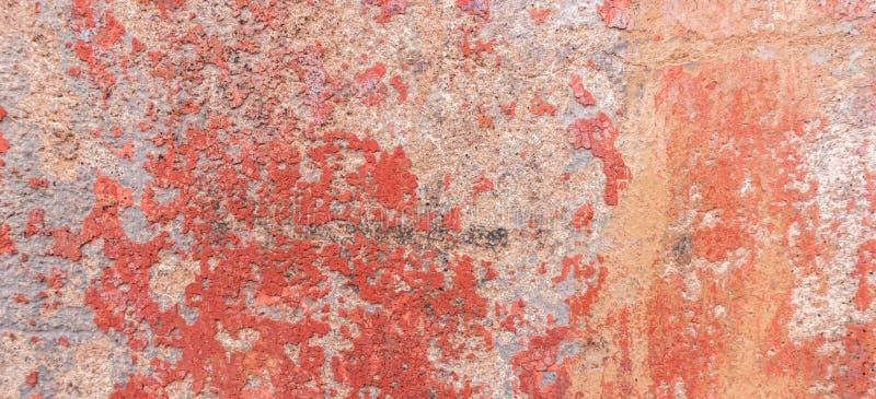 Alte verwitterte gemalte Wandhintergrundbeschaffenheit Rote schmutzige abgezogene Gipswand mit herunterfallen blättert von der Fa stockbild