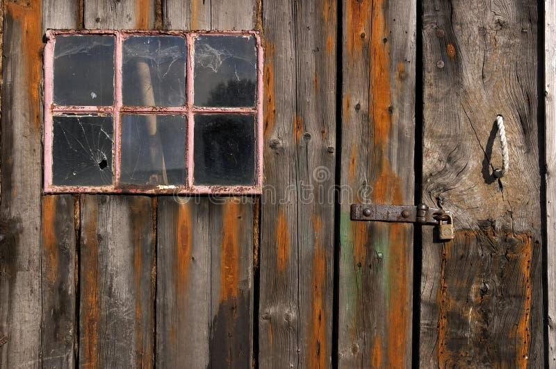 Alte verwitterte und getragene hölzerne Planken mit Tür und rosafarbenem gestaltetem Fenster lizenzfreie stockbilder