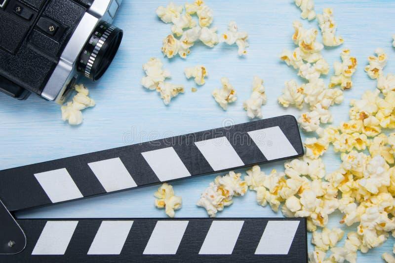 alte Videokamera und Rahmen für das Filmen, vor dem hintergrund des zerstreuten Popcorns lizenzfreies stockbild