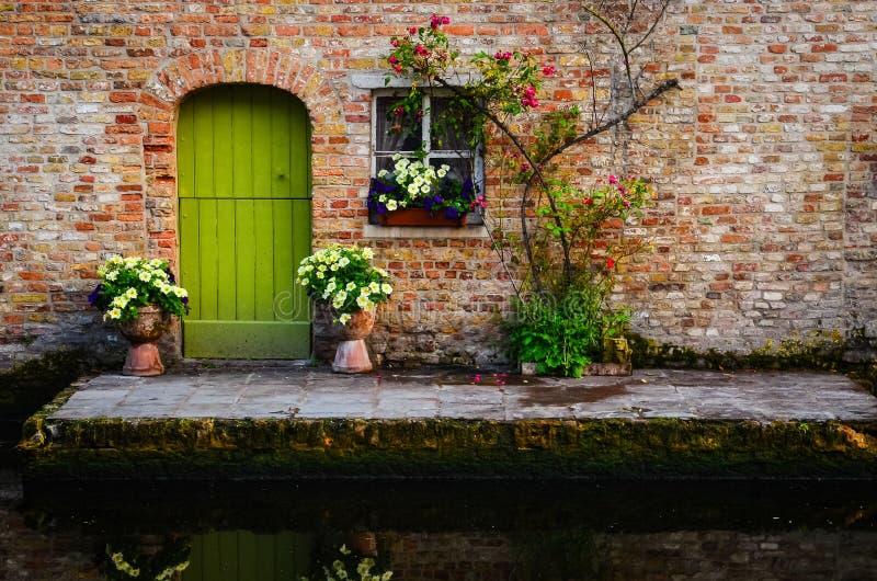 Alte Wand der Weinlese mit grüner Tür und Blumen stockfotografie