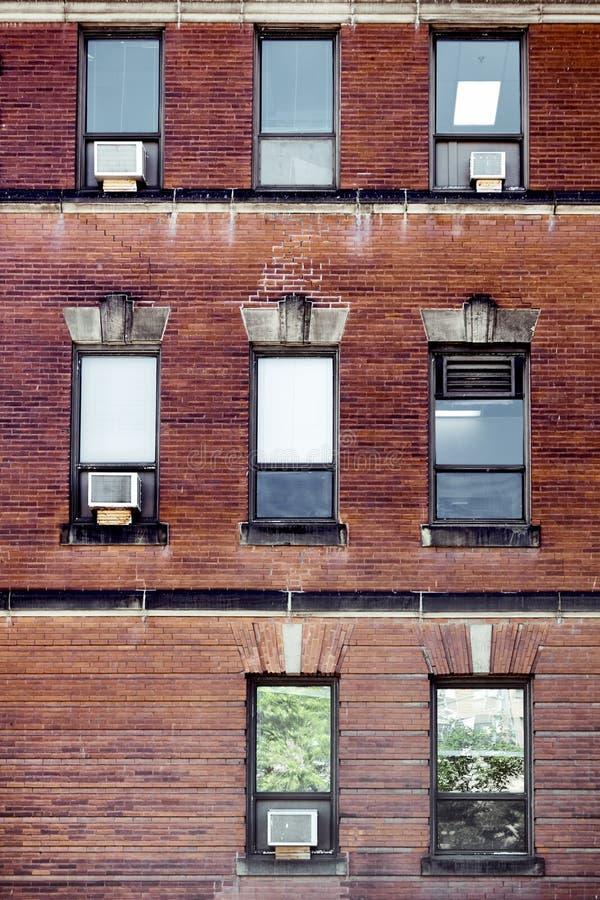 Alte Wand des roten Backsteins mit den Rechteckfenstern und -klimaanlagen angebracht in Montreal, Kanada stockfoto