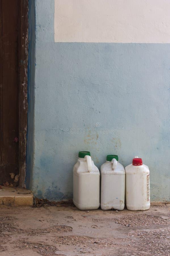 Alte weiße Flaschen Insektenvertilgungsmittel nahe bei einer Wand lizenzfreies stockbild