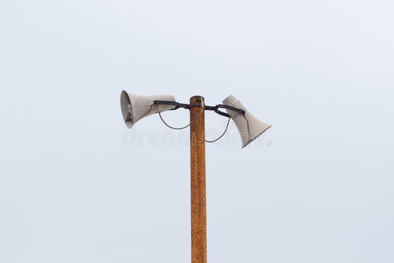 Alte weiße Lautsprecher im Freien, Megaphone auf einem rostigen Metallpfosten stockbild