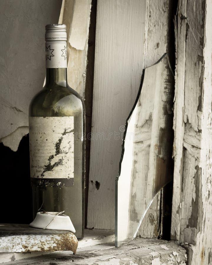 Alte Weinflasche in einem alten Haus stockbild