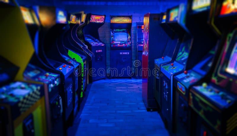 Alte Weinlese Arcade Video Games in einem leeren dunklen Spielraum mit Blaulicht mit gl?henden Anzeigen stockfoto
