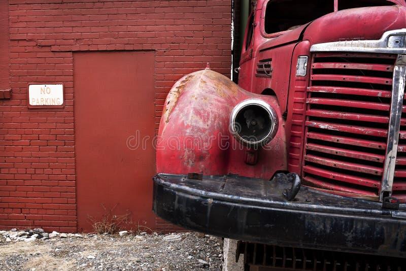 Alte Weinlese-Kramfünfziger jahre rotes Löschfahrzeug verließ geparkt vor Backsteinbau in der Stadt stockfoto