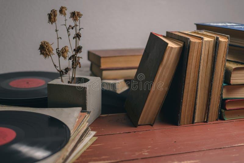 Alte Weinlesebücher, Vinylaufzeichnungen und eine trockene Blume in einem konkreten Vase stockfotografie
