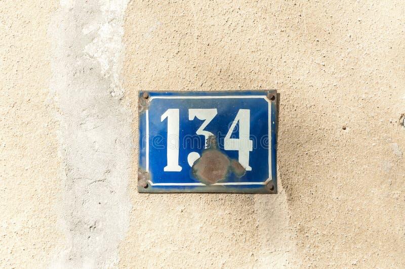 Alte Weinlesehaus-Adreßmetallplattenzahl 134 hundert vierunddreißig auf der Gipsfassade der verlassenen Ausgangsaußenwand stockfotos