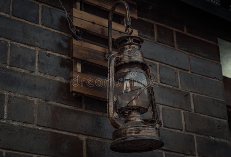 Alte Weinlesekerosin-Petroleumlaternelampe, die auf der Ziegelsteinwand hängt stockfoto