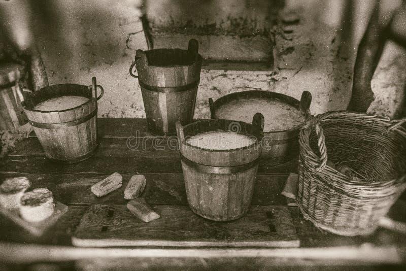 Alte Weise der Herstellung von Käse- und Tagebuchprodukten, von Eimern von Milch, von Creme und von gesäuerter Milch auf Holztisc lizenzfreie stockfotos