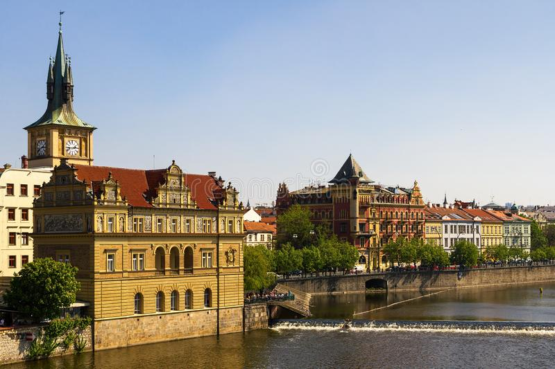 Alte Werbung und Wohngebäude und eine Kirche entlang die Moldau-Fluss in Prag lizenzfreies stockbild
