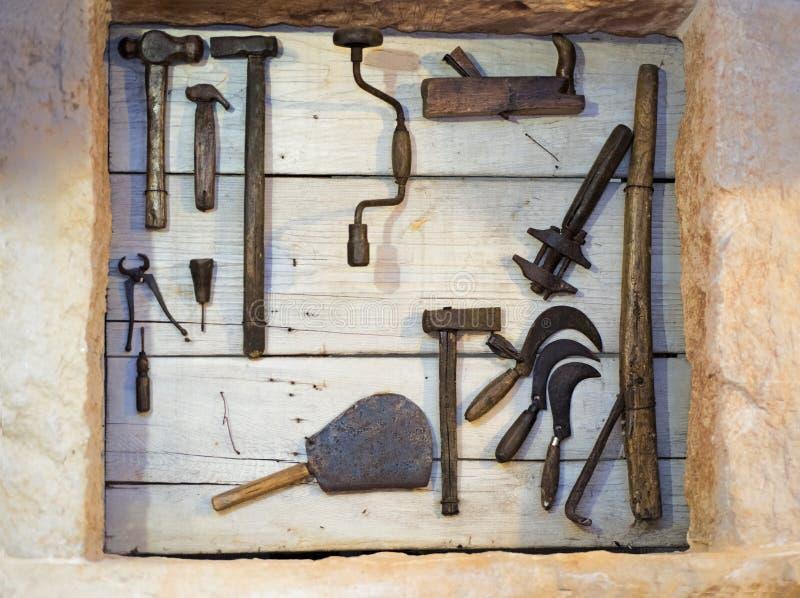 Alte Werkzeugsammlung auf hölzerner Wand stockfotografie