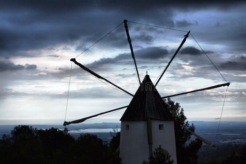 Alte Windmühle, die zum bewölkten Sonnenunterganghorizont schaut stockbilder
