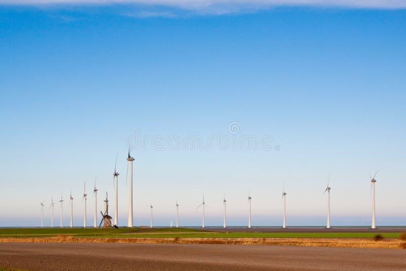 Alte Windmühle und neue Windmühlen stockfoto