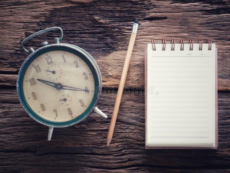 Alte Winduhr mit Notizbuch und Bleistift auf hölzerner Tabelle im Weinlesefarbschema stockbild