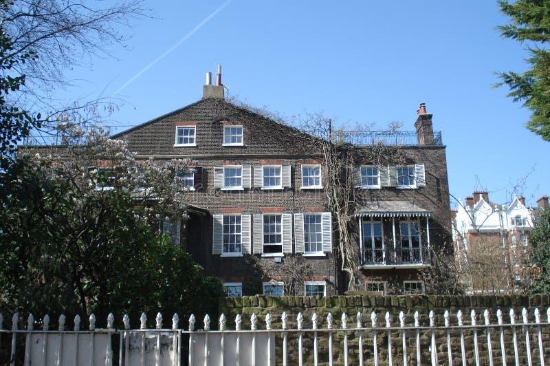 Alte Wohngebäudefassade mit mehrfachen weißen Schiebefenstern und Garten lizenzfreie stockfotos