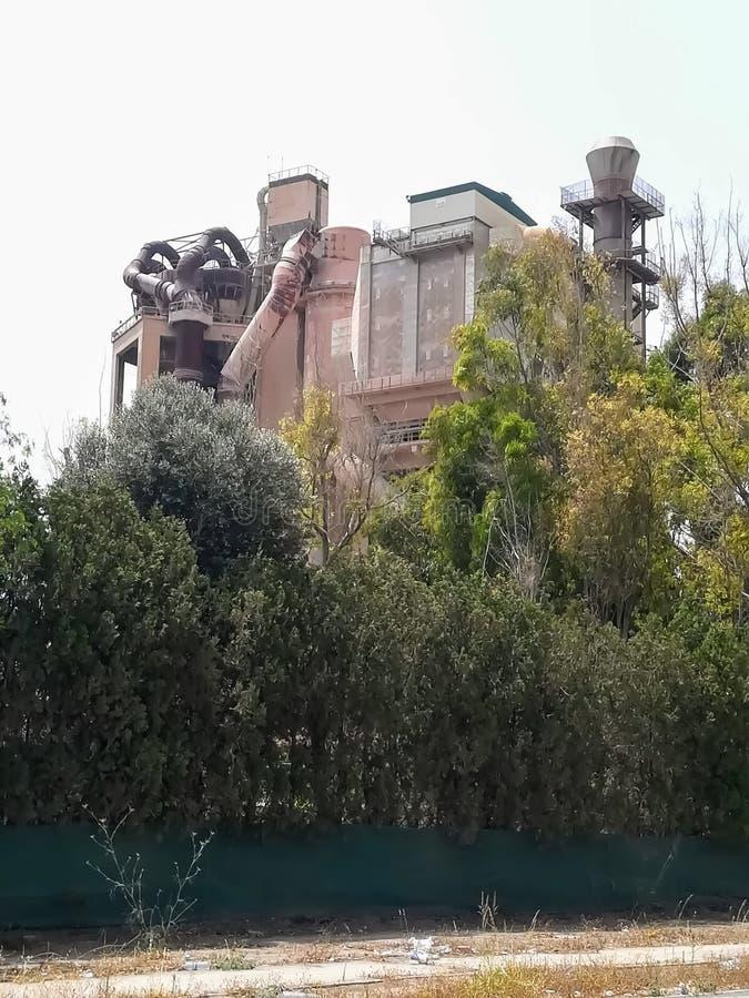 Alte Zementfabrik versteckt hinter Bäumen lizenzfreie stockbilder