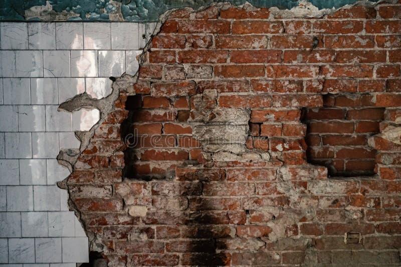 Alte zerstörte Wand mit Ziegelsteinen und Fliese stockfoto