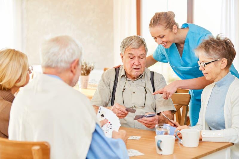 Altenpflegerin et cartes de jeu d'aînés photos stock