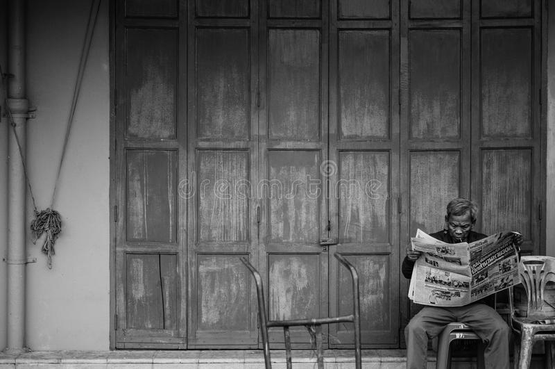 Alter älterer asiatischer Mann sitzen Lesezeitung vor altem vint stockbilder