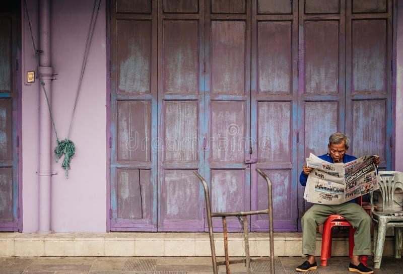 Alter älterer asiatischer Mann sitzen Lesezeitung vor altem vint stockfoto