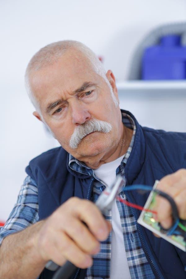 Alter älterer Mann, der eigenhändig Draht über Zangen schneidet lizenzfreie stockbilder